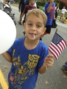 kid with american flag and white balloon