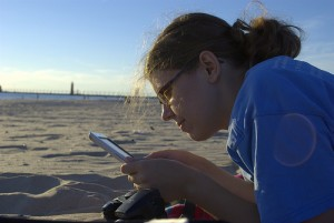 young woman on beach with e-reader