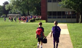two elementary school kids walking into a suburban school