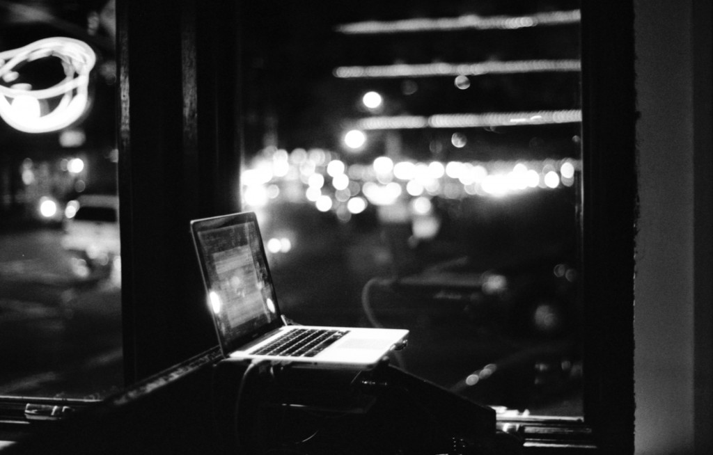 Black and white artistic photo of a lone laptop on a city scene backgorund
