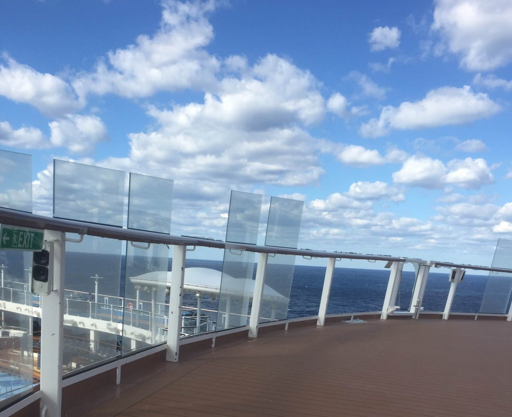 cruise ship deck under fluffy white clouds and blue skies
