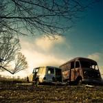 dilapidated vans against sky backdrop