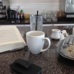 breakfast counter with coffee cup, book and water glass