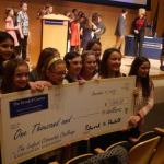 5th graders holding up a sign that is a huge check for 1000 dollars