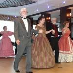 Ladies and gentleman indoors dressed in civil war era clothes -still shot of a line dance