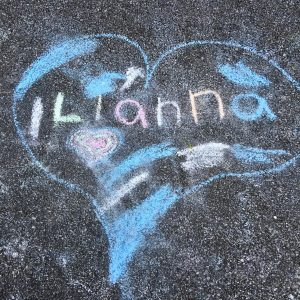 "A blue chalk heart with a smaller, multicolored heart inside it. ""ILianna"" is written across the heart in multicolored chalk. Patches of blue and pink fill the heart"