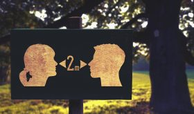 "silhouette sign of two people's profiles with a ""2m"" word with arrows pointing out from either side between the profiles"