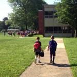 two elementary school kids walking into a suburban school
